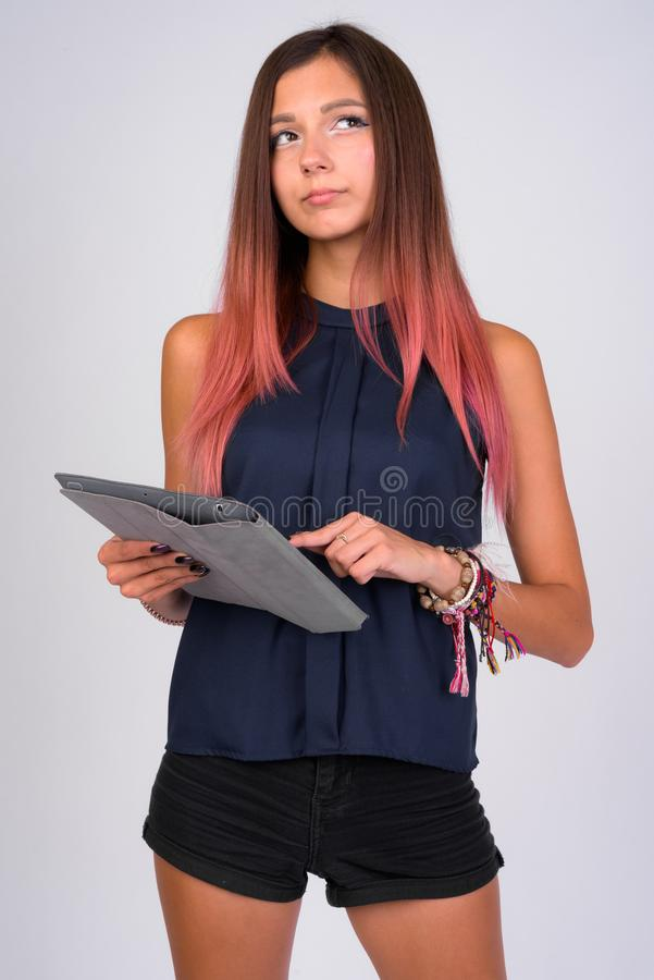 Portrait of young beautiful businesswoman thinking while using digital tablet stock image