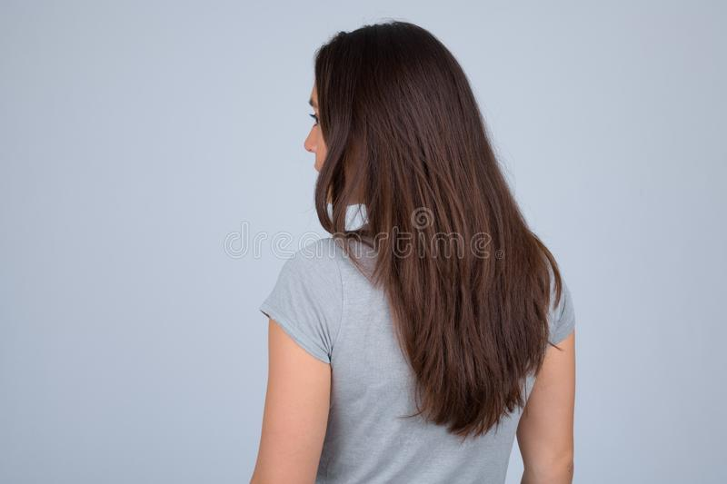 Rear view of young multi-ethnic woman against white background. Studio shot of young beautiful multi-ethnic woman wearing casual clothes against white background royalty free stock photo