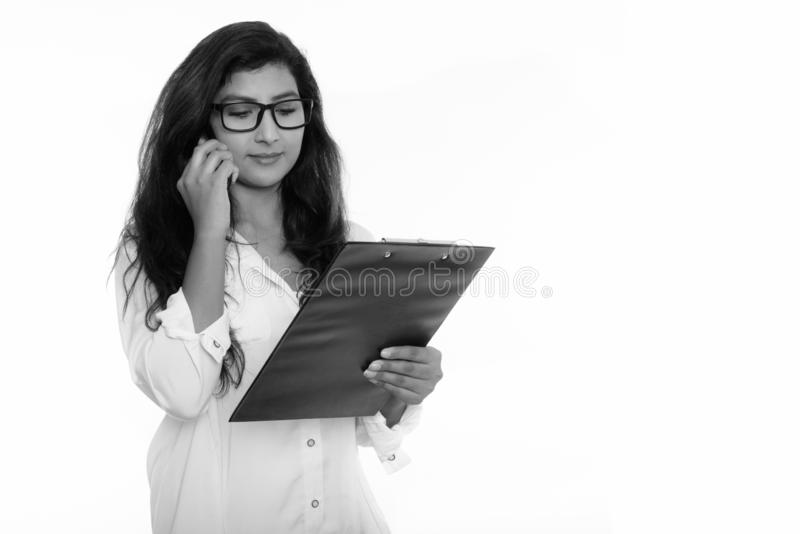 Studio shot of young beautiful Persian woman talking on mobile phone while reading on clipboard royalty free stock photos