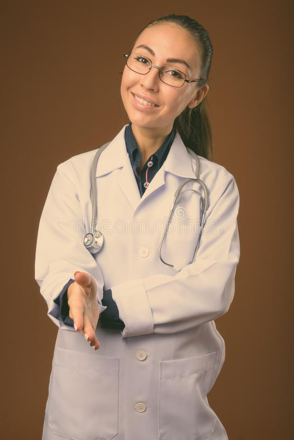 Studio shot of young beautiful woman doctor against brown background royalty free stock image