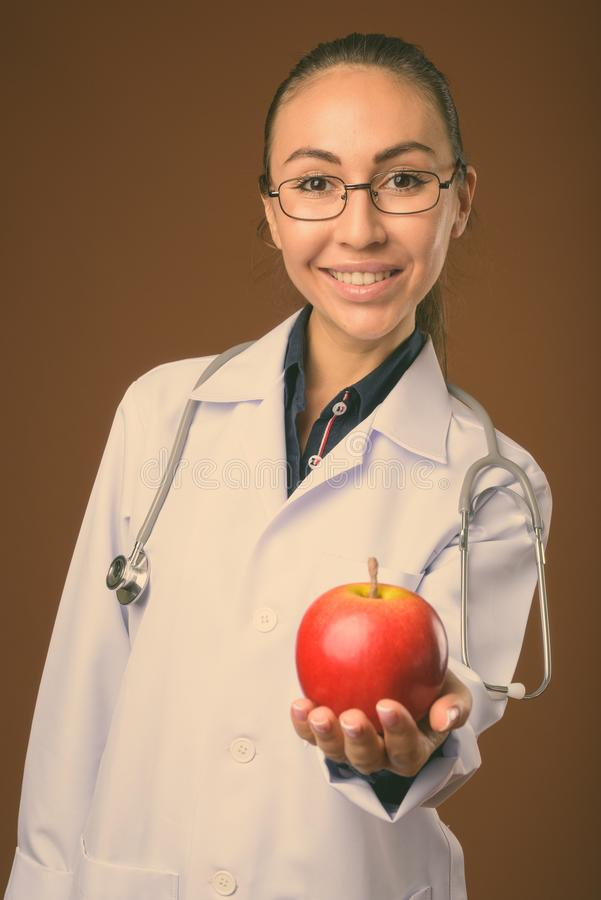 Studio shot of young beautiful woman doctor against brown background stock image