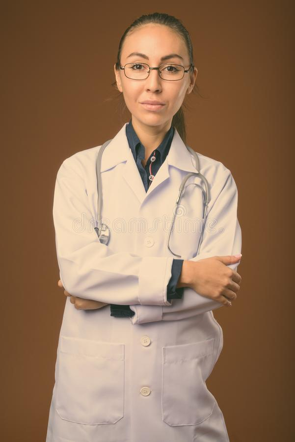 Studio shot of young beautiful woman doctor against brown background royalty free stock photos