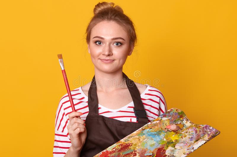 Studio shot of young beautiful woman wearing wite casual shirt with red stripes and brown apron on yellow background. Pretty. Blonde woman holds alette and royalty free stock photo