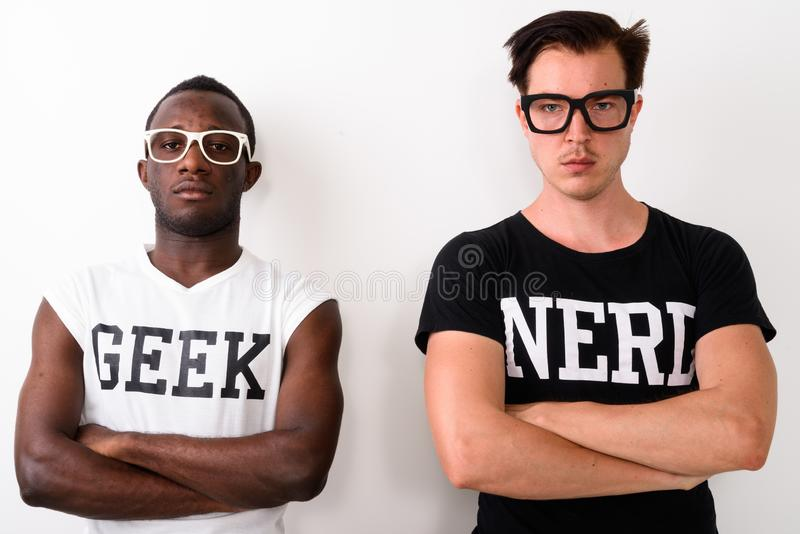 Studio shot of young black African Geek man with European Nerd m. An against white background royalty free stock image