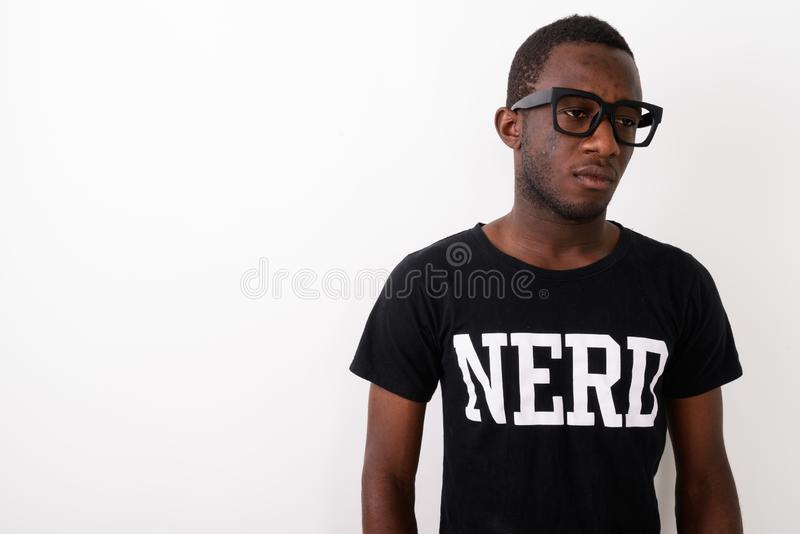 Studio shot of young black African geek man wearing Nerd shirt w. Hile thinking against white background stock photos