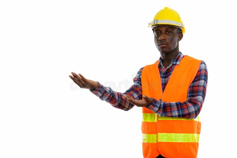 Studio shot of young black African man construction worker showi royalty free stock photos