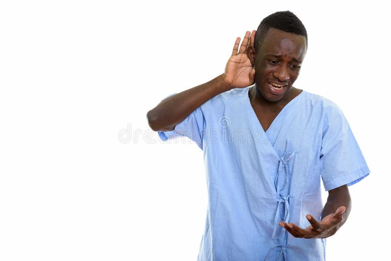 Studio shot of young black African man patient looking angry whi. Le listening royalty free stock photos