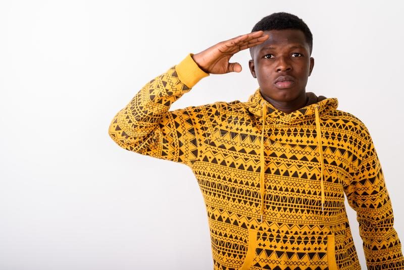 Studio shot of young black African man saluting against white ba. Ckground stock image