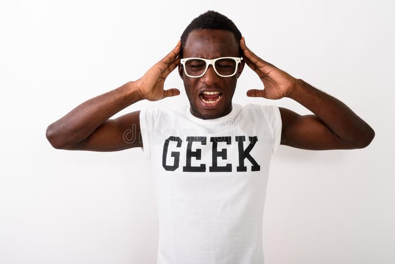Studio shot of young black African nerd man wearing Geek shirt w. Studio shot of young black African nerd man wearing Geek shirt against white background royalty free stock photos