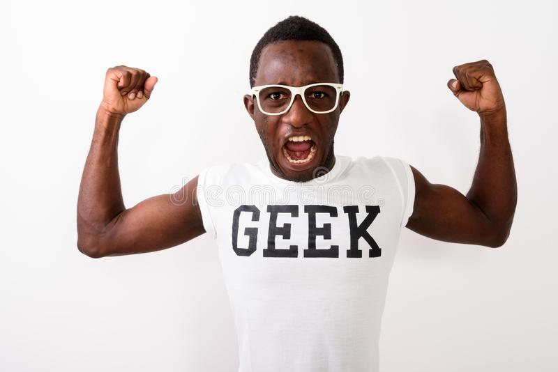Studio shot of young black African nerd man wearing Geek shirt w. Hile flexing his arms and showing bicep muscles against white background royalty free stock photos
