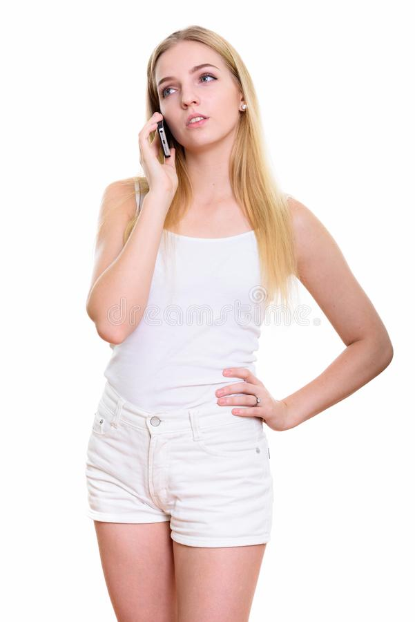 Studio shot of young bored teenage girl talking on mobile phone stock photography