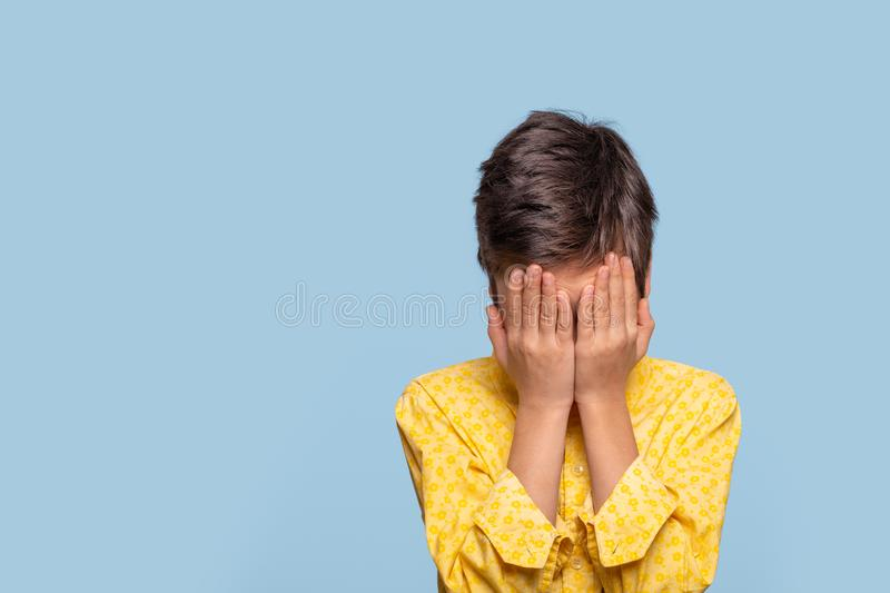 Studio shot of a young boy covering his face in sadness someone's feeling down today against   blue background with copy space royalty free stock photo