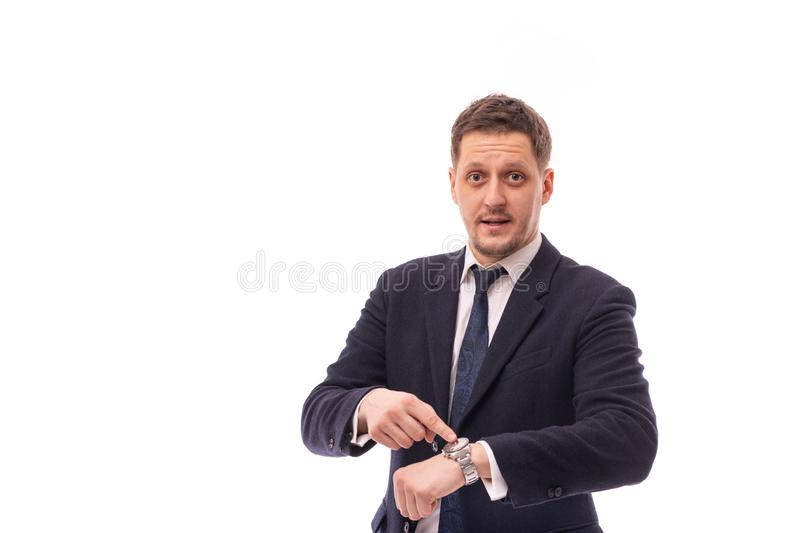 Studio shot of a young businessman wearing dark blue suit points to time on a wristwatch recalling the necessary discipline or stock photography