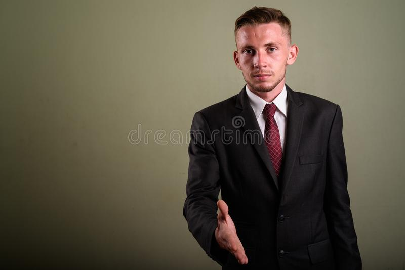 Young businessman wearing suit against colored background. Studio shot of young businessman wearing suit against colored background royalty free stock photography