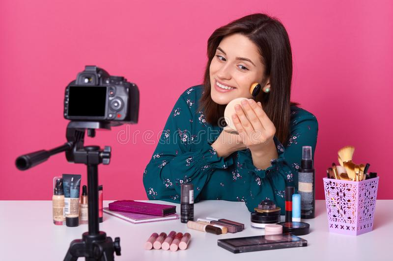 Studio shot of young Caucasian woman , advertising new beauty products, online translation, using brush to apply powder, wearing royalty free stock photography