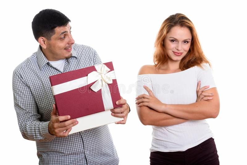 Young Hispanic couple in love with man opening gift box looking surprised. Studio shot of young couple in love with men looking at women while opening gift box stock images