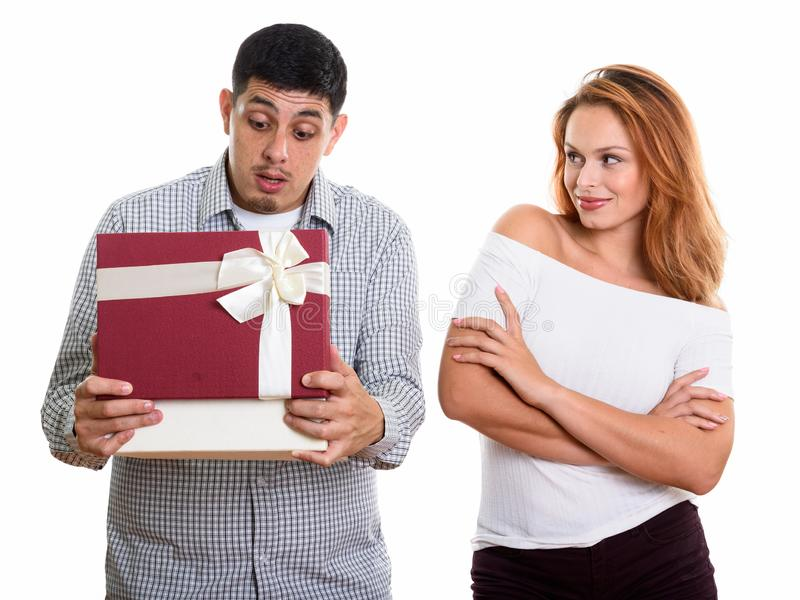 Young Hispanic couple in love with man opening gift box looking surprised. Studio shot of young couple in love with men opening gift box looking surprised stock photo