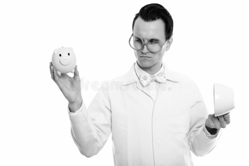 Studio shot of young crazy man doctor holding empty coffee cup while looking at piggy bank royalty free stock photography