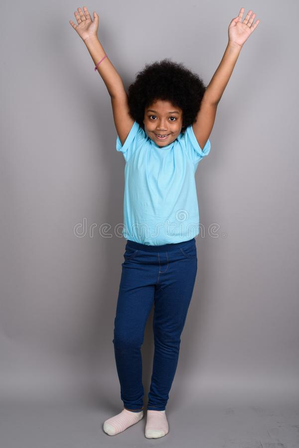 Young cute African girl against gray background stock image