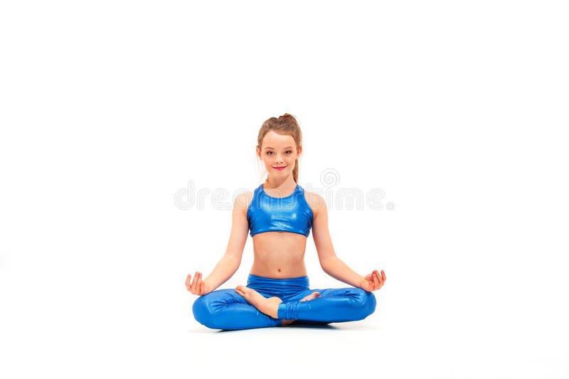 Studio shot of a young fit girl doing yoga exercises on white background royalty free stock photo
