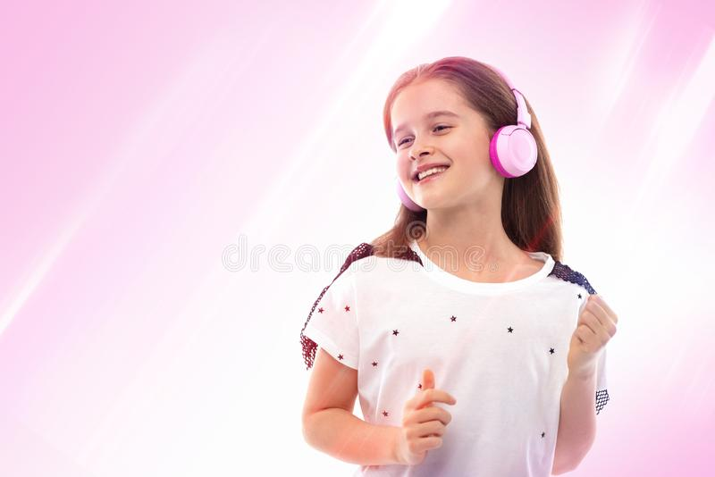Studio shot of a young girl  on a color background.  She is standing in pink headphones listening to music and smiling stock photos