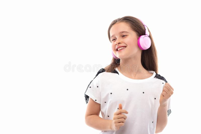 Studio shot of a young girl  on a white background.  She is standing in pink headphones listening to music and smiling royalty free stock photos