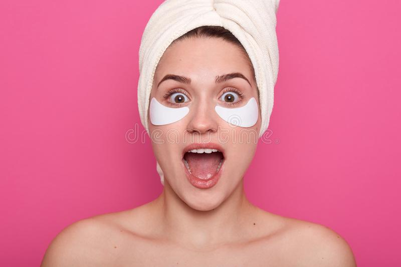 Studio shot of young girl wearing white on head and with bared shoulders, posing with opened mouth, having surprised facial stock photography