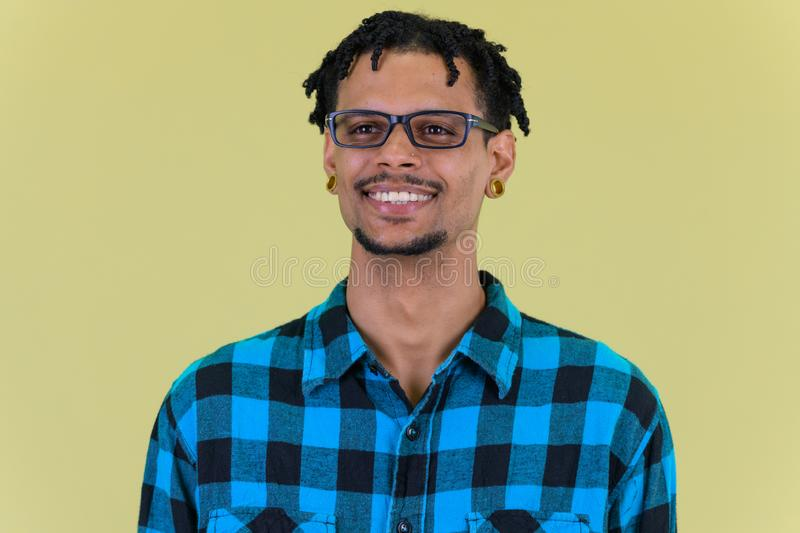 Face of young happy African hipster man thinking stock image