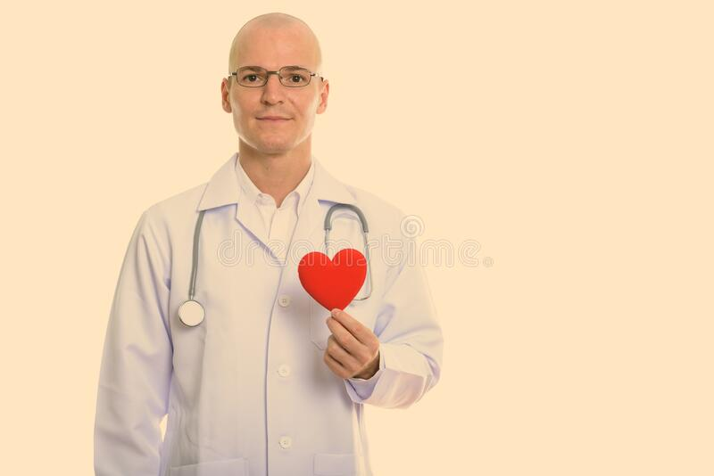 Studio shot of young handsome bald man doctor holding red heart stock image