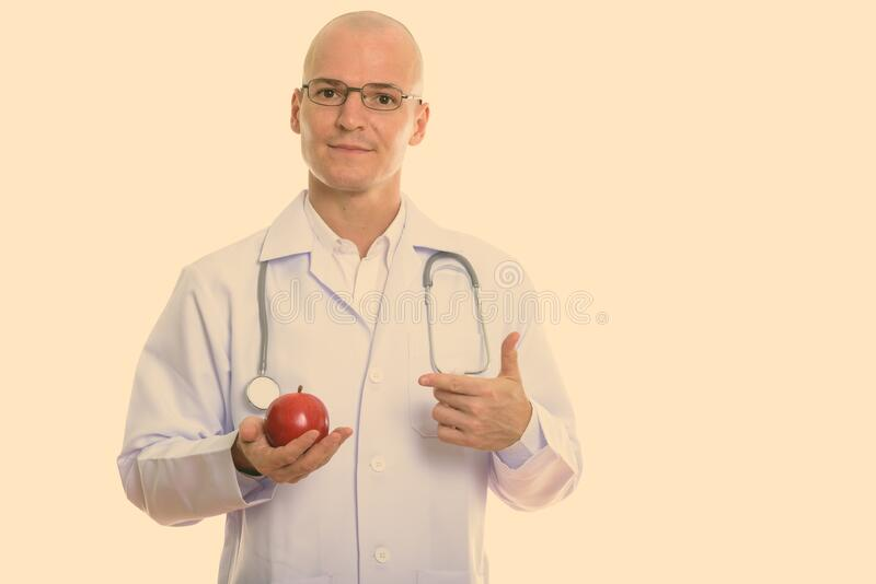 Studio shot of young handsome bald man doctor holding and pointing at red apple royalty free stock photography