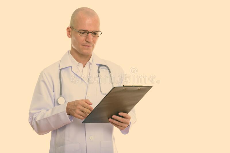 Studio shot of young handsome bald man doctor reading on holding clipboard stock photos
