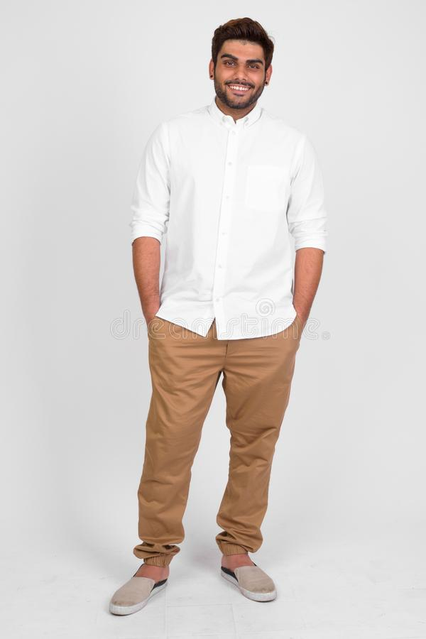 Full body shot of happy young bearded Indian man smiling stock photography