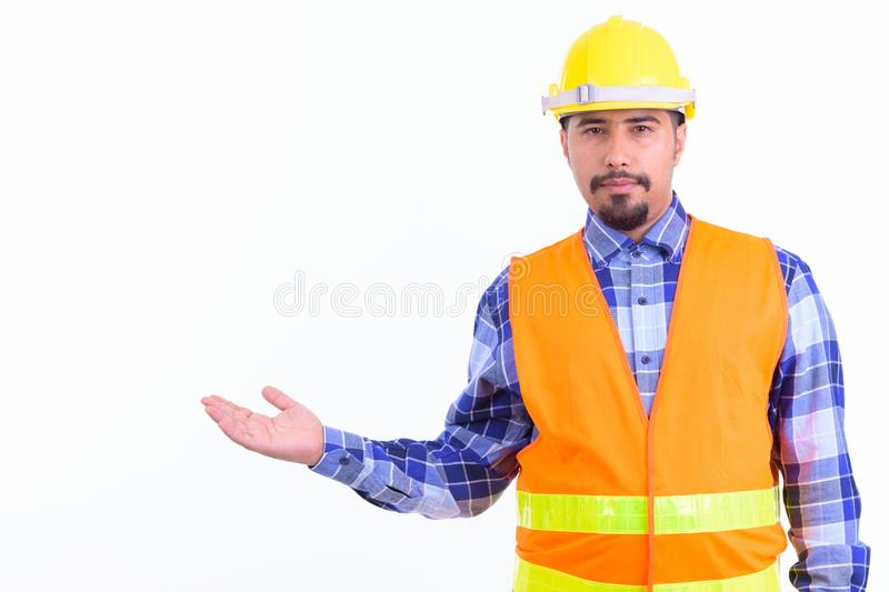Bearded Persian man construction worker showing something. Studio shot of young handsome bearded Iranian man construction worker isolated against white royalty free stock photography