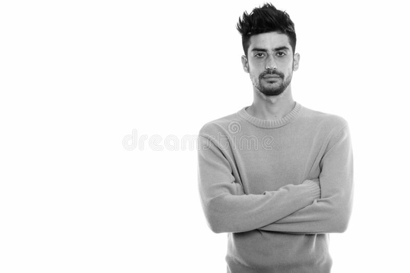 Studio shot of young Persian man with arms crossed royalty free stock images