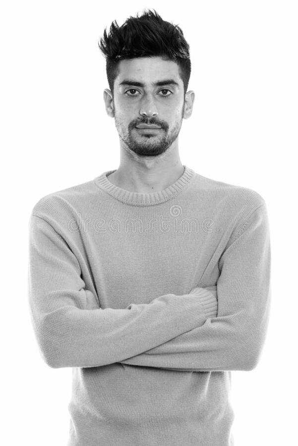 Studio shot of young Persian man with arms crossed stock photos