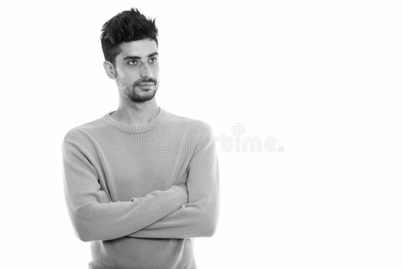 Studio shot of young Persian man thinking with arms crossed royalty free stock photos