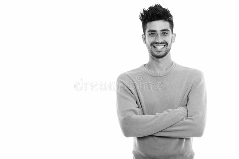 Studio shot of young happy Persian man smiling with arms crossed royalty free stock image