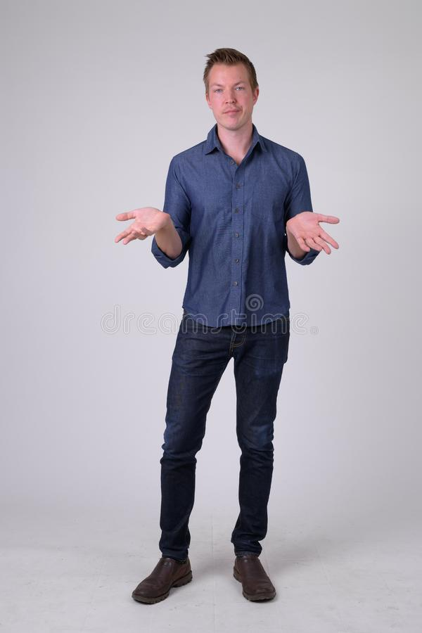 Full body shot of confused young businessman shrugging shoulders. Studio shot of young handsome businessman against white background royalty free stock photo