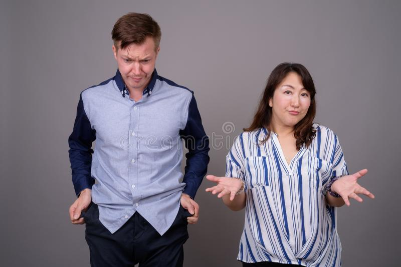 Portrait of multi ethnic diverse couple in studio with money problems. Studio shot of young handsome businessman and mature Asian businesswoman against gray royalty free stock images