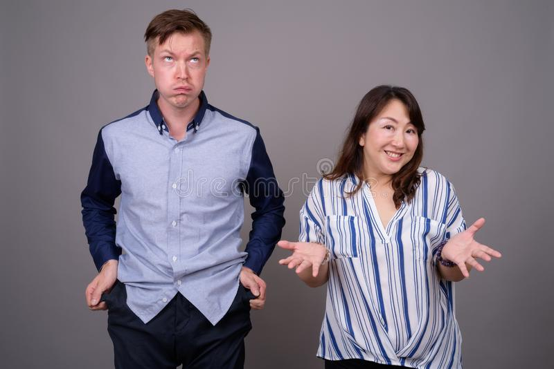 Portrait of multi ethnic diverse couple in studio with money problems. Studio shot of young handsome businessman and mature Asian businesswoman against gray royalty free stock photo