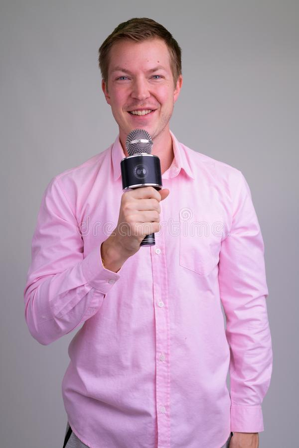 Happy young handsome businessman as host with microphone stock image