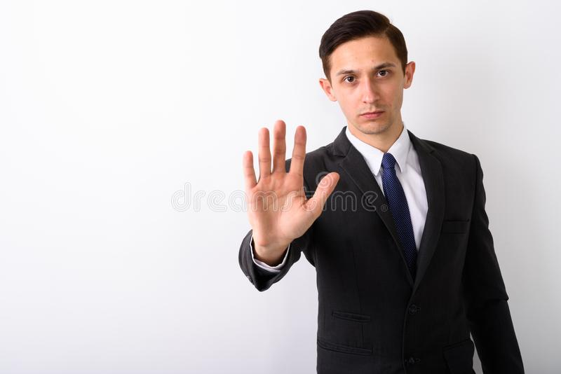 Studio shot of young handsome businessman showing stop hand sign. Against white background royalty free stock image