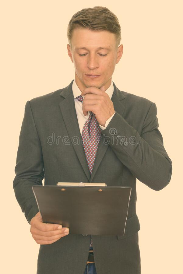 Studio shot of young handsome Caucasian businessman reading clipboard and thinking stock photos