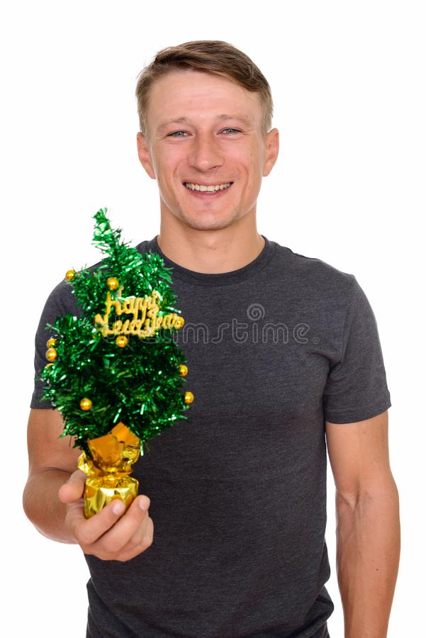 Studio shot of young handsome Caucasian man holding Happy New Ye royalty free stock image