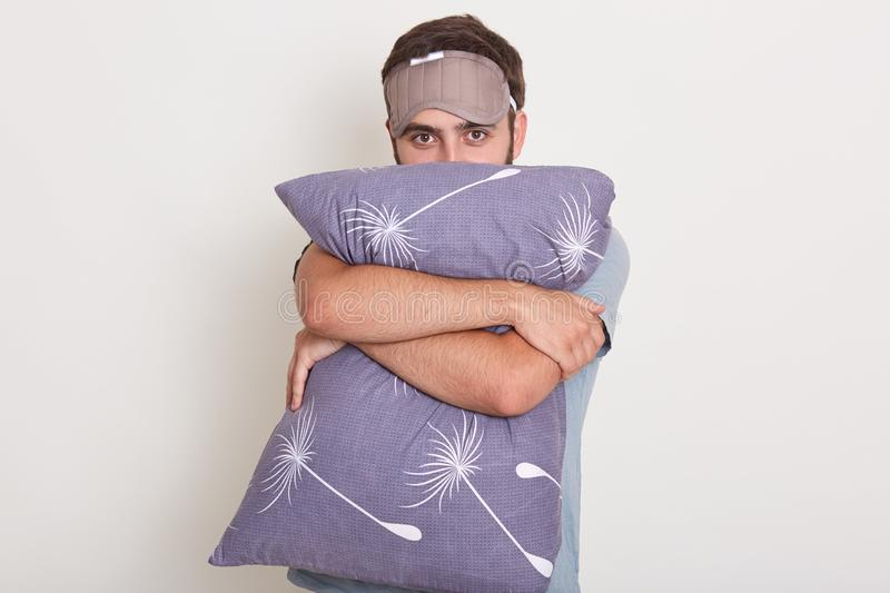 Studio shot of young handsome guy on white background wearing t shirt, holding pillow in his hands, male hugging his pillow, ready stock photo