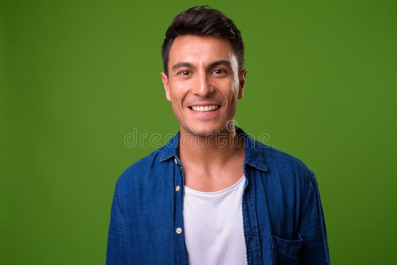 Young handsome Hispanic man against green background. Studio shot of young handsome Hispanic man against chroma key with green background stock images