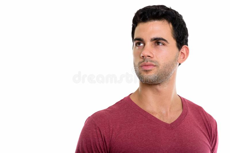 Studio shot of young handsome Hispanic man thinking while lookin. G up stock photos