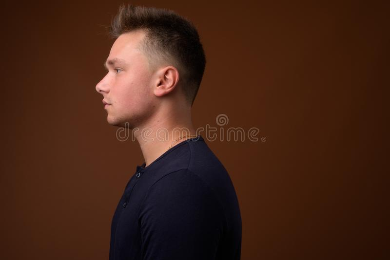 Studio shot of young handsome man against brown background royalty free stock photos