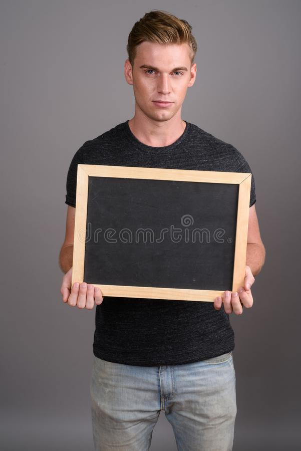 Young handsome man with blond hair wearing gray shirt against gr stock photos