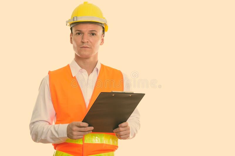 Studio shot of young handsome man construction worker holding clipboard royalty free stock photography